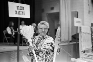 Nana Wray of Callaway, Virginia holding a couple of her hand made brooms. (Scrub mop in right hand, hearth broom in left.)