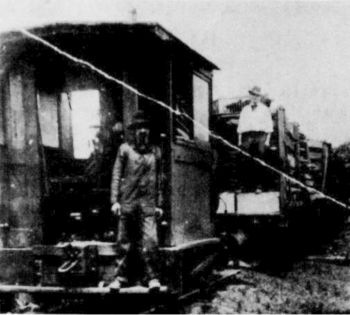 Photo of the small 0-4-0. In foreground is Seward Sine, Alex Barton is standing on the freight car.