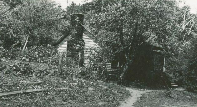 Image shows a house surrounded by trees and shrubs, with a dirt road crossing in front of it and a small dirt path leading to its front door. The house appears to be of older construction. Image taken by R.F.E. on August 28, 1936. Image taken near milepost 170 of the Blue Ridge Parkway, near Rocky Knob, Va.