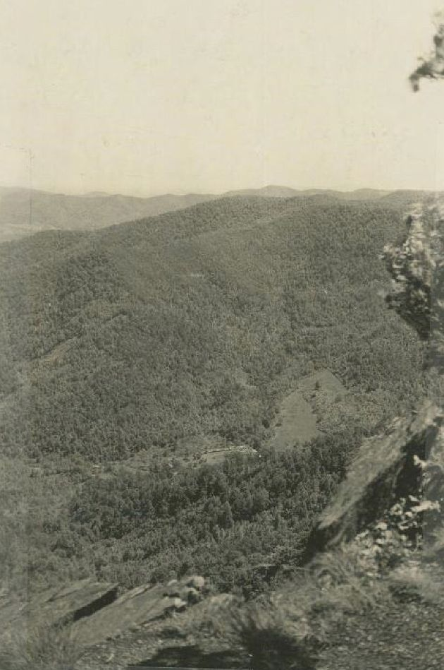 Image shows a Civilian Conservation Corps camp from a distance, in a valley below as seen from the top of Rocky Knob. An open clearing and small buildings can be seen in the valley at the center of the photograph. Image taken by Edward H. Abbuehl in May of 1938. Image taken in Rocky Knob Park near milepost 168.5.