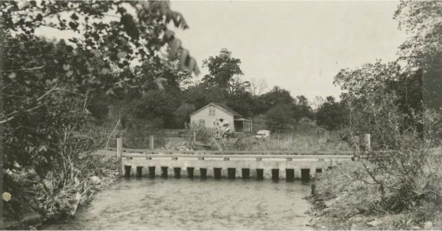 Image shows a high water ford at a camp site built by the Civilian Conservation Corps. A small house stands in the background, past the ford. Image taken by Robert G. Hall in May of 1938. Image taken near Rocky Knob, Va., and milepost 168 of the Blue Ridge Parkway.