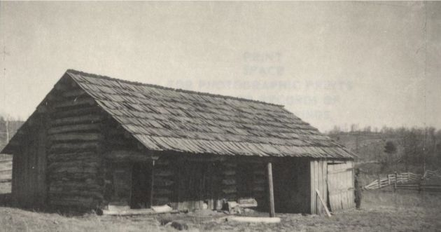 Image of the front exterior of a log barn in the Mabry Mill area near milepost 176.1, section 1T of the Blue Ridge Parkway. A man is near the right of the barn. Image taken from the National Park Service, Blue Ridge Parkway Headquarters. Photographed by Dale on March 6, 1939.