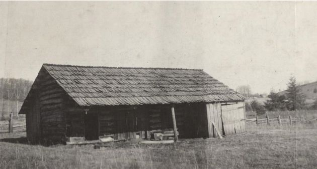 Image of the front exterior of a log barn in the Mabry Mill area near milepost 176.1, section 1T of the Blue Ridge Parkway. A split rail fence can be seen behind the barn. Image taken from the National Park Service, Blue Ridge Parkway Headquarters. Photographed by Dale on March 5, 1939.