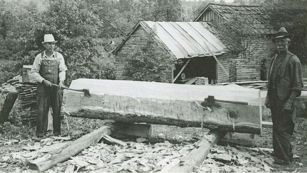 Alonzo Newton Hylton on right, unknown on left, using axes to chop a large piece of timber as part of the mill's water-wheel construction. Image taken from the National Park Service, Blue Ridge Parkway Headquarters. Photographed by Kenneth McCarter in June 1942.