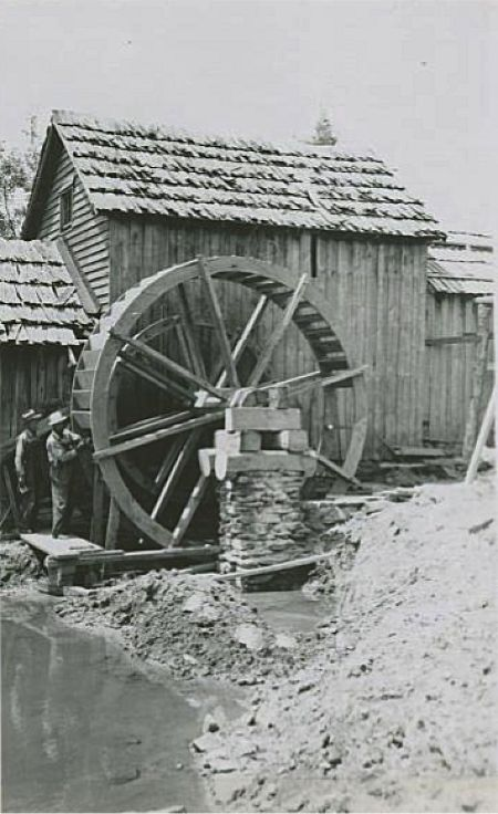 Image of a worker attaching a paddle of the Mabry Mill water-wheel while another worker looks on near milepost 176.1, section 1T of the Blue Ridge Parkway. The water-wheel is mid-construction, with about three-fourths of the paddles in place. The area surrounding the mill is littered with debris most likely from the construction. Image taken from the National Park Service, Blue Ridge Parkway Headquarters. Photographed by Kenneth McCarter in July 1942.