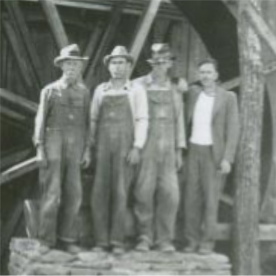 Alonzo Newton Hylton on left, others unknown, standing in front of the mid-constructed Mabry Mill water wheel near milepost 176.1, of the Blue Ridge Parkway. Image taken from the National Park Service, Blue Ridge Parkway Headquarters. Photographed by Kenneth McCarter in July 1942.