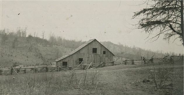 Image of a wooden barn with a catslide roof, located near Station 1338 and milepost 159.4 in Section 1R of the Blue Ridge Parkway. The image shows some of the surrounding land, as well as a wooden fence which passes in front of the barn. Image taken by Robert G. Hall on March 28, 1939.