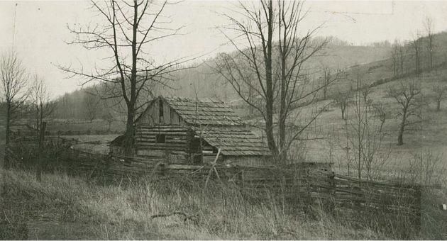 Image shows a wooden barn, constructed of logs and with a shake or shingled roof. There is lean-to constructed at either side of the barn. The barn is located at the bottom of a hill, and a wooden fence runs along one side of it and encloses the land around it. The Blue Ridge Mountains are visible in the background. Image was taken near Station 1210 and milepost 158.8 in Section 1R of the Blue Ridge Parkway. Image taken by Robert G. Hall on March 28, 1939.
