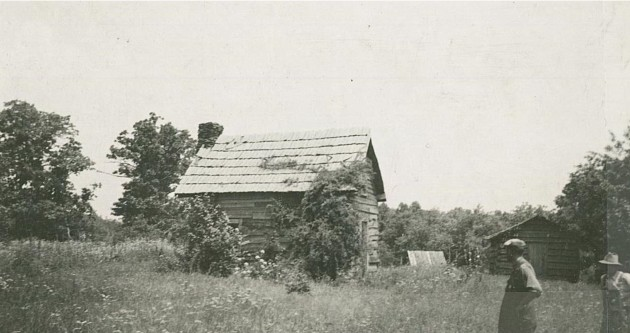 This photograph shows the Puckett Cabin and outbuildings with two individuals in the foreground, near milepost 189.8 in section 1U. The photograph was taken on July 25, 1939 by Dale Sipes.  Puckett Cabin House recommended retained as is.