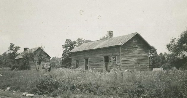 This photograph shows two wooden cabins alongside the road, near milepost 189.8 in section 1U. Two persons are in the photograph in front of the smaller structure on the left. The photograph was taken on July 25, 1939 by Dale Sipes. Building group which state proposed to remove. Puckett group. House on right was RAZED.